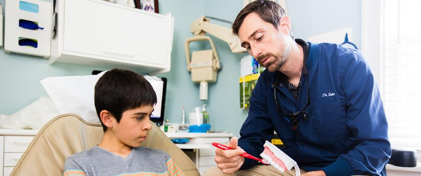 Dentist and young male patient talking about proper dental care.